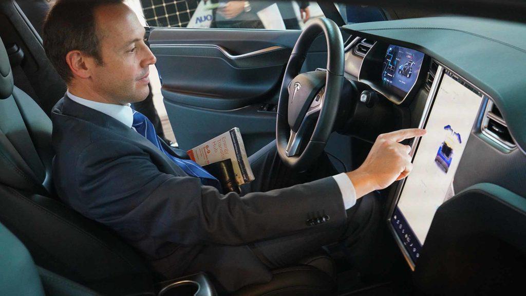 Businessman operating a Tesla Model X touchscreen
